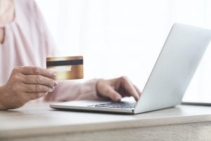 Cropped image of old woman making purchasing online